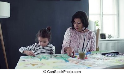 A small girl with grandmother sitting at table at home,...