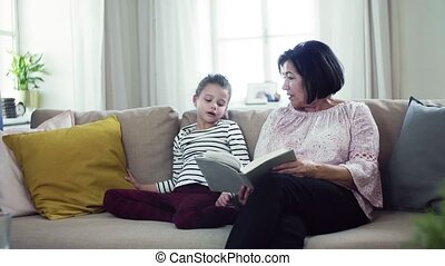 A small girl with grandmother sitting on sofa at home,...