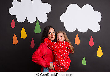 A small girl with her mother on a black background with clouds and raindrops.