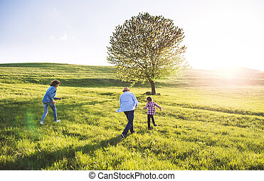 A small girl with her senior grandparents playing outside in nature.