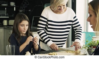 A small girl with mother and grandmother at home. - A small...