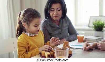 A small girl with mother and grandmother sitting at table at...