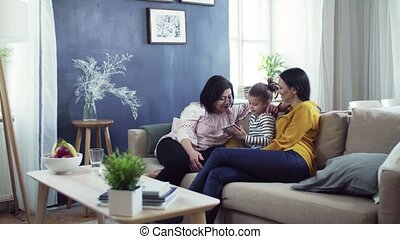 A small girl with mother and grandmother sitting on sofa at...