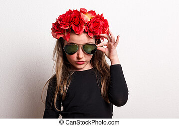 A small girl with red flower headband and sunglasses in a studio.