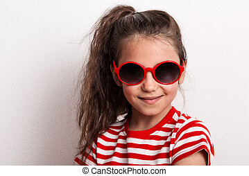 A small girl with red sunglasses and striped T-shirt standing in a studio.