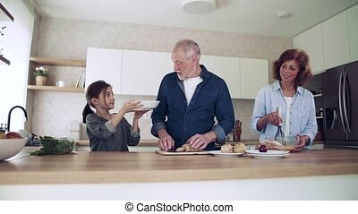 A small girl with senior grandparents indoors in kitchen ...