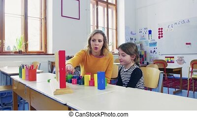 A small girl with teacher learning at school. - A small girl...