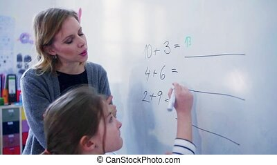 A small girl with teacher writing on the whiteboard at school.