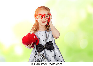 A small glamorous girl with red glasses and a dog talking on the phone