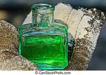 a small glass bottle with green liquid stands on the palm of a gloved hand