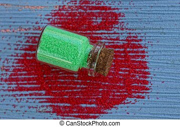 glass bottle with green sand lies on a blue table in red sand