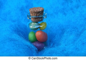 a small glass decorative bottle with colored pebbles stands in a blue wool fabric