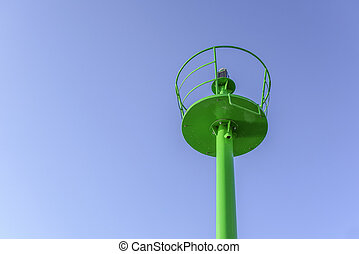A small green lighthouse on the waterfront.