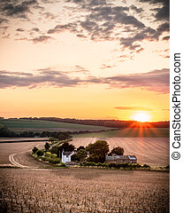 a small hamlet of country houses surrounded by wheat fields st sunset