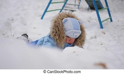 a small happy child plays on the Playground in winter