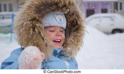 a small happy child plays with snowflakes in the park