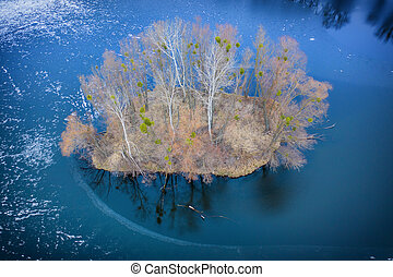 A small island in the center of a frozen lake. Autumn landscape.