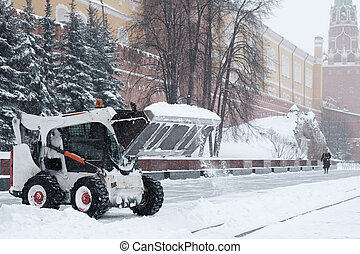 A small loader excavator bobcat removes snow from the sidewalk near the Kremlin walls during a heavy snowfall.