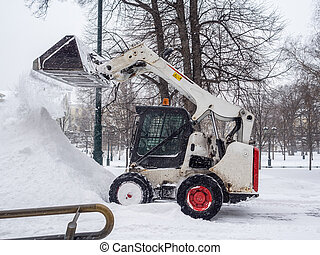 A small loader with a bucket pours snow into a large pile in a city park