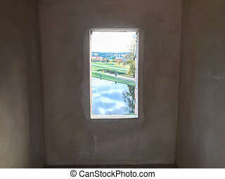 A small narrow black window with a frame on an old ancient stone white thick concrete wall in an old castle. The background