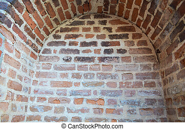A small narrow recess, a niche with an arch on an old ancient stone red thick brick wall in an old castle. The background