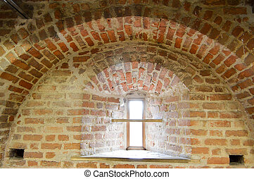A small narrow window on an old, ancient, cracked stone shabby brick wall of red brick in the basement. The background