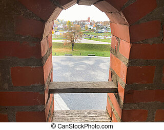 A small narrow window on an old ancient stone thick brick wall in an old castle. The background
