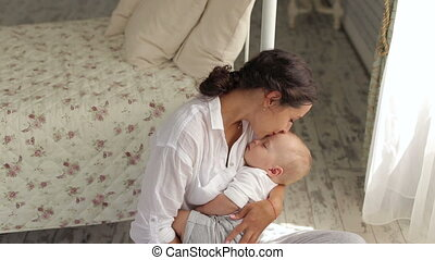 A small newborn baby sleeps in his mother's arms in the bedroom.