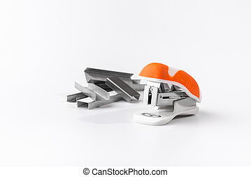 A small orange stapler and staples on a white background. Close-up. Copy space. Space for text