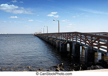 A small pier with anonymous people walking