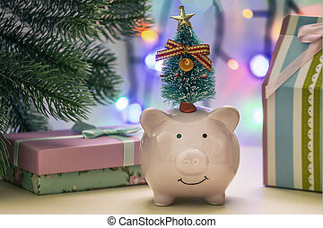 A small piggy bank with a tree on his head. In the background, gifts and garland in blur.