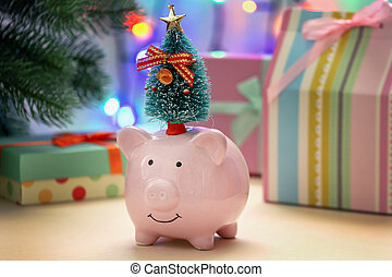 A small pink piggy bank with a tree on her head. In the background, a Christmas garland and gifts in blur.