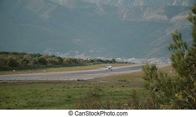 a small plane sits on the landing strip on the background of the mountains in Montenegro