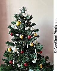 A small plastic Christmas tree decorated with toys stands in the apartment against the background of the wall.