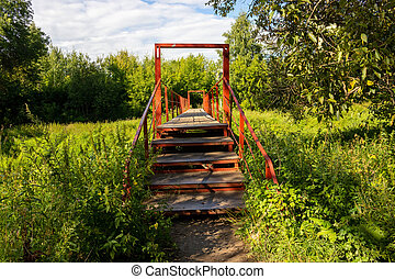 A small red bridge with wooden flooring and iron arches over a small forest river