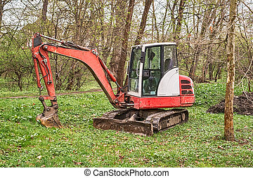 a small red excavator in the woods