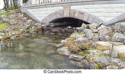 A small river flows under a stone bridge