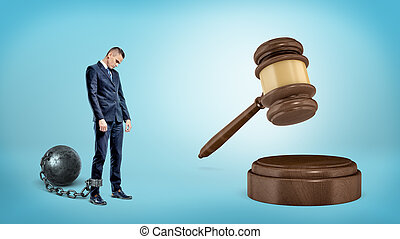 A small sad businessman leashed to an iron ball stands near a giant hitting judge gavel.