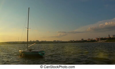 A small sailboat on the quay in the city bay, sunset,...