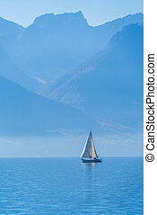 A small sailing yacht on the Lake Geneva and the Alps, Switzerland