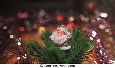 A small silver figure of Santa Claus stands near a red Christmas Hanging Bauble on artificial Christmas tree. Christmas garlands blink in the foreground and background. Side view.