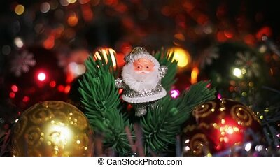 A small silver figure of Santa Claus stands near a red Christmas Hanging Bauble on artificial Christmas tree. Christmas garlands blink in the foreground and background.