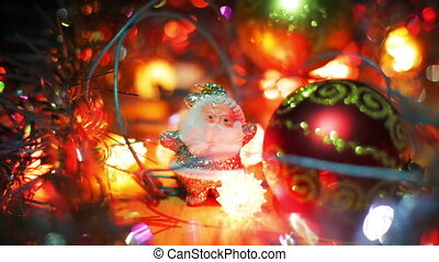 A small silver figure of Santa Claus stands near a red Christmas Hanging Bauble on the table. Christmas garlands blink in the foreground and background.