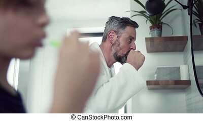 A small son with father brushing teeth in the bathroom in...