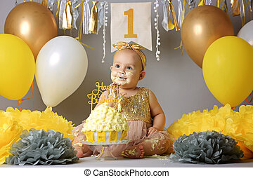 a small, sweet baby girl in a golden dress with a bow on her head trying a jazzy jelly cake from a cream. studio shot of a birthday on a gray background surrounded by balls