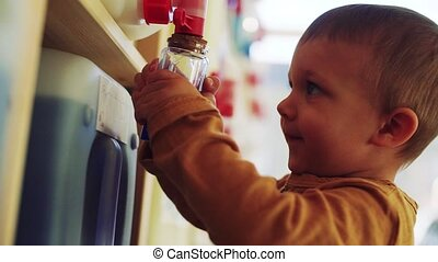 A small toddler boy standing by dispensers in zero waste...