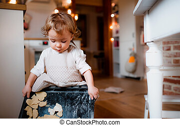 A small toddler girl making cakes on the floor in the kitchen at home.