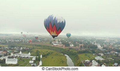 A small village - a lot of colorful air balloons flying in...