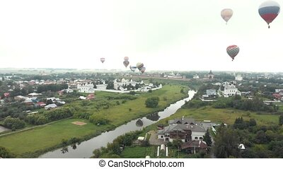A small village - huge air balloons flying in the sky -...