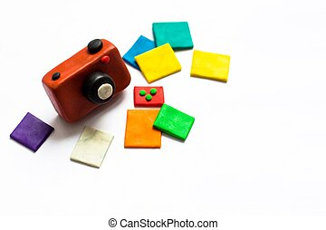 A small vintage camera of brown color is made of plasticine. Next to the camera is a few photos of bright and colorful flowers. The whole composition lies on a white background.